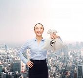 business and money concept - young businesswoman holding money bags with euro