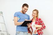repair, building and home concept - smiling couple with clipboard, wallpaper roll and ladder
