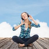 music and technology concept - smiling young woman sitting on floor and listeting to music with head