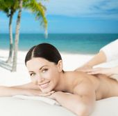 spa, resort and vacation concept - smiling woman in spa salon getting massage