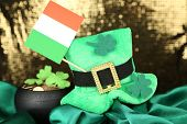 Saint Patrick day hat, pot of gold coins and Irish flag on shiny background