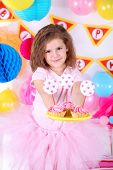 Pretty little girl with cakes celebrate her birthday
