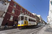 Lisbon, Portugal - September 15, 2013: The iconic number 28 Tram line with an old Lisbon Tram crossing the medieval, Alfama District.