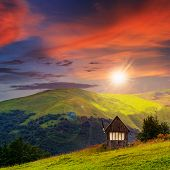 Village On Hillside Meadow With Forest In Mountain At Sunset