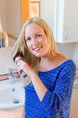 a young woman is familiar with a brush her long blond hair in the bathroom