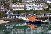 stock photo of outboard engine  - lifeboat reflected in the water of Brixham harbour - JPG