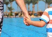 Mother and child holding hands on vacation looking at swimming pool concept for family vacations, child safety and single parent holiday