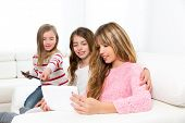 three kid sister friends girls group playing together with tablet pc on white sofa