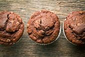 top view of chocolate muffins on old wooden background