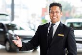 happy young indian car dealer standing inside showroom