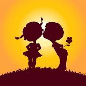 Sunset silhouettes of kissing boy and girl