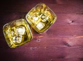 Top Of View Of Two Glasses Of Whiskey With Ice On Old Wood Table Background
