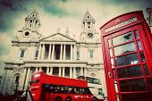 St Paul's Cathedral in London, the UK. Red bus and telephone booth, cloudy sky. Symbols of London in