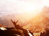 stock photo of breathtaking  - A happy man sitting on the peak of a mountain with hands raised admiring breathtaking view at sunset - JPG