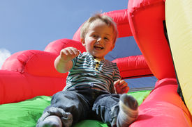 stock photo of inflatable slide  - 2 year old boy jumping down the slide on an inflatable bouncy castle - JPG