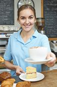 Waitress In Cafe Serving Customer With Coffee