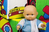 picture of baby doll  - toy baby doll sitting next to cubes
