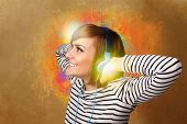 Pretty young woman with headphones listening to music in front of a painted wall