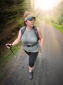 Overweight woman walking in nature. Healthy lifestyle and weight loss concept.