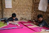 KUMROKHALI, INDIA - JAN 16: Indrajit, 17 and Anandalok, 15, Naskar working on the decoration of text
