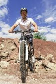 stock photo of prosthesis  - Shot of young male mountain bike rider with leg prosthesis between rocks - JPG