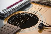 picture of risque  - Headphones on guitar Writing music and book - JPG