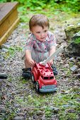 picture of fire truck  - A toddler playing with a toy fire truck outside in the summer - JPG