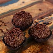 stock photo of bonbon  - Brazilian chocolate truffle bonbon brigadeiro on wooden table - JPG