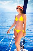 Beautiful young woman with perfect body relaxing on the sailboat, wearing vivid yellow swimsuit, enj