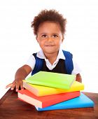 Happy African preschooler sitting behind desk with many books on it, isolated on white background, e