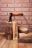 Firewood and axe on floor on brick background