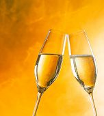A Pair Of Champagne Flutes With Golden Bubbles On Golden Light Background