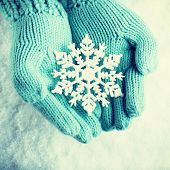 Woman hands in light teal knitted mittens are holding a beautiful snowflake in a snow background. Love and St. Valentine concept.  Instagram filter.