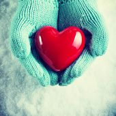 Woman hands in light teal knitted mittens are holding a beautiful glossy red heart in a snow background. Love and St. Valentine concept.