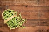 a basket of fresh green French beans on a rustic barn table, top view