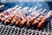 stock photo of barbie  - Pork on skewers cooked on barbecue grill - JPG