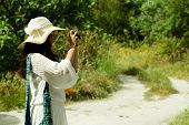 young woman photographer taking photo, summer day in Greece