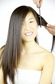 Asian Woman Getting Hair Combed By Stylist