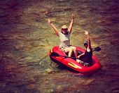 image of raft  - two girls floating down a river in an inflatable raft toned with a retro vintage instagram filter effect  - JPG