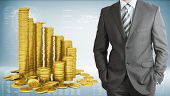 Businessman with pyramid of gold coins