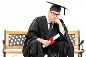 Angry college graduate holding a diploma isolated against white background