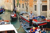Several Gondolas With Tourists In A Narrow Channel. Venice, Italy