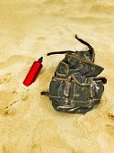 stock photo of canteen  - Backpack and canteen water bottle in the sand of a beach - JPG
