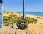 stock photo of beach hut  - Backpack and shoes on the porch of a wooden hut next to the shore of a European beach. Backpacking traveller taking a break in a tour through Algarve Portugal. (Tavira beach in Tavira island)
