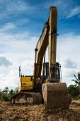 picture of backhoe  - Yellow backhoe on the mound - JPG