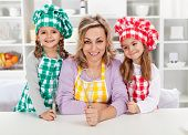 Woman and her little helper chefs in the kitchen, ready for some cooking or baking