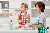 Grumpy kids ordered to do the dishes - by a parent pointed finger