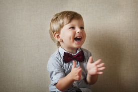stock photo of vivacious  - Beautiful little boy wearing a stylish maroon bow tie laughing and clapping his hands against a grey wall with vignetting - JPG