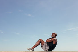 stock photo of abdominal  - Side view of fitness model doing crunches against blue sky - JPG