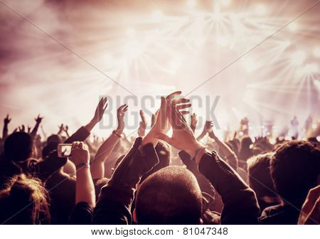 Vintage style photograph of a group, upbeat individuals getting a charge out of rock show, raised up